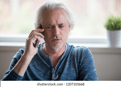 Close up of serious aged man talking on phone from home, thoughtful senior male speak over cellphone, having discussion with colleague, elderly use smartphone having cell conversation