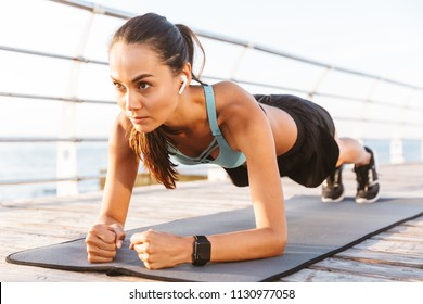 Close up of a serious asian sportswoman in earphones doing plank exercise outdoors at the beach