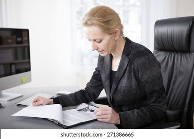 Close up Serious Blond Businesswoman at her Office Scanning Business Documents with Magnifying Glass.