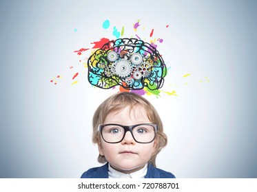 Close up of a serious boy wearing a suit and glasses and standing near a gray wall with a colorful brain sketch with gears on it.