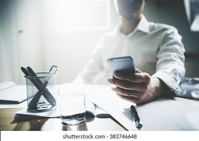 Close up of serious and concentrated businessman using his smart phone at ofiice. Cropped image of male hands with modern cellphone.Filtered image, business concept