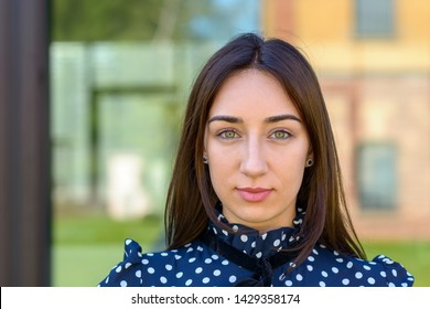 Close up of an serious demure stylish young woman in a stylish blue and white outfit and copy space
