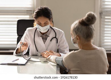 Close up serious female doctor wearing face mask measuring checking old woman blood pressure, using digital tonometer, medical checkup, elderly generation healthcare and insurance concept