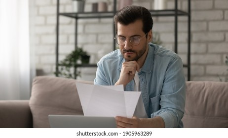 Close up serious man wearing glasses reading letter, payment notification, holding paper, checking financial documents, focused businessman working with correspondence, sitting on couch at home
