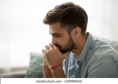 Close up of serious millennial man sit on couch thinking about problem solution, focused male lost on thoughts making decision on considering something, thoughtful guy pondering over issue or trouble