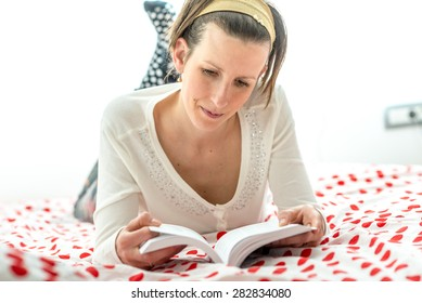 Close up Serious Pretty Woman Lying on her Stomach on her Bed While Reading a Book.