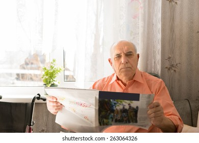 Close up Serious Senior Man Holding Tabloid Looking at the Camera While Sitting Inside his House.