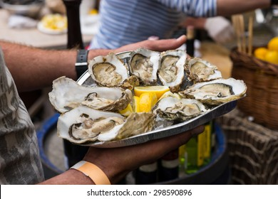 Close Up of Server with Tray of Fresh Shucked Oysters with Lemon Served as Appetizer