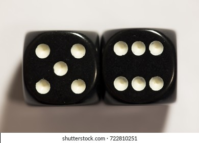 Close up of a set of black six-sided dice, top-down view, with eleven pips showing.
