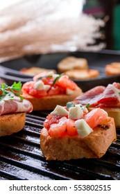 Close up of set of bruschetta on black grill background. Tasty antipasto.