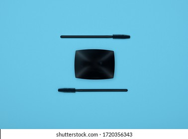 Close up set of face makeup black mascara brushes and eye shadows over blue background, elevated top view, directly above