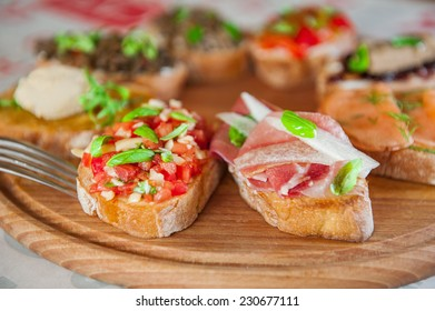 Close up Set  of Italian Apetizer Bruschettas with tomato, chopped vegetables and prosciutto ham on the wooden board