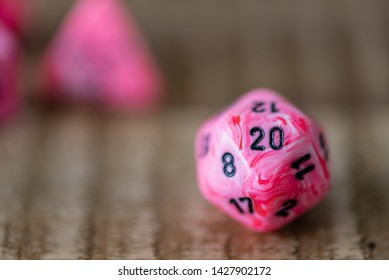 Close up of a set of pink and white marbled dice, used for tabletop role playing games. The image is focused on a twenty sided die (d20) with the 20 clearly visible.