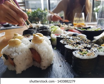 Close up of set of sushi rolls on a table in a restaurant. A group of friends eating sushi rolls using bamboo sticks.