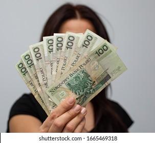 Nahaufnahme mehrerer Banknoten mit einem Nennwert von 100 PLN polnischem Geld, Zloty in einer Fanform in den Händen von Frauen auf grauem Hintergrund