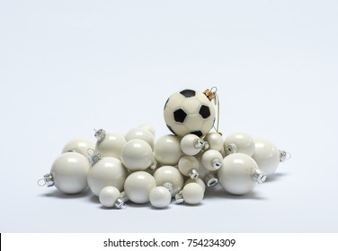 Close up of several creamy white and one soccer ball shaped Christmas tree baubles against a white background (landscape orientation)