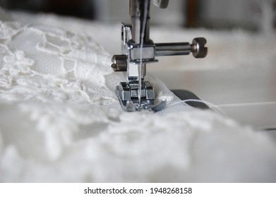 Close up of a sewing machine making alterations of a bride's wedding dress.