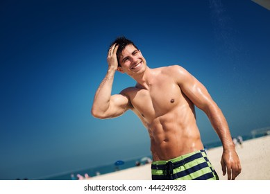 Close up of sexually attractive handsome man taking shower and feeling glad.