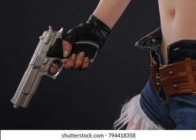 Close up of sexy girl with gun in hand. Studio shoot