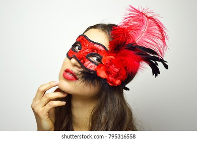 Close up of sexy woman in mysterious Venetian mask looking at camera. Attractive girl with red flowery carnival mask. Beauty female ready for carnival night party pose on white background. Copy space.