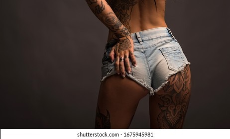 close up of sexy woman wearing short jeans and tattoos against dark background.