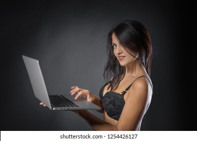 Close up of Sexy young brunette woman in black sensual lingerie using laptop and posing on black background wall in studio.