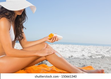 Close up of sexy young woman on the beach applying sun cream
