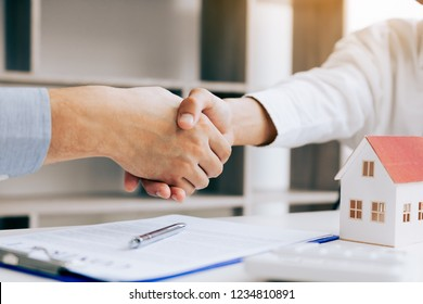 Close up of shaking hands with customer and real estate broker after signing a contract in home office.