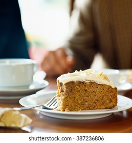 Close up of Sharing carrot cake at coffee shop on plate with person sitting in the background