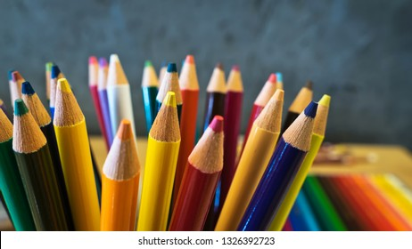 Close up of Sharpened wooden colored pencils on dark gray background. Shallow depth of field.