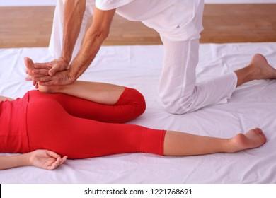 Close up of Shiatsu leg massage on female patient dressed in red.