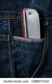 Close up of shiny blues harmonica in the blue jean pocket,musical concept and beautiful objects