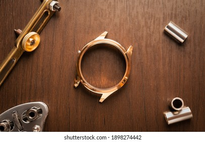 Close up of shiny golden stainless steel watch case waiting for repairing, vintage wood watchmaker table with tool and equipment for service background concept