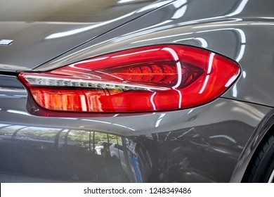 Close up of shiny gray paint of modern luxury sports car with reflection on rear bumper after wash & wax. Concept of car detailing and paint protection background.