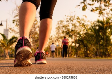 Close up shoe of runner feet running on road at public park.Woman fitness jog workout wellness concept.