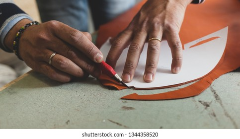 Close up of a shoemaker cutting leather. Concept of shoes designer.
