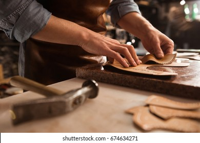 Close up of a shoemaker working with leather textile and hammer at a workshop