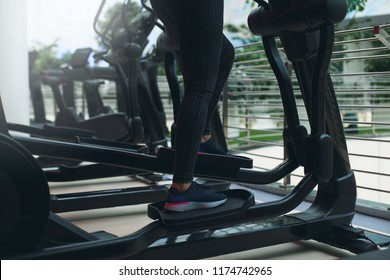Close up shoes woman's legs feet on cycling machines workout at fitness gym. Cropped view of attractive sport woman using an elliptic trainer. Doing cardio in sports club.