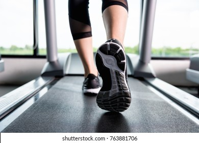 Close up  shoes woman's muscular legs feet running on treadmill workout at fitness gym