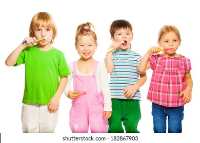 Close shoot of four happy little 3-4 years old kids standing with toothpaste