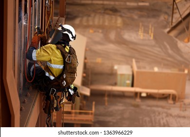 Close up shoot of rope access stick welder wearing full body safety harness equipment, abseiling working at height conducting welding chute parent repairs on construction site Perth, Australia