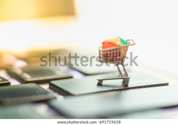 Close up of shopping cart or trolley miniature figure toy on laptop computer. Shopping, retail and e-commerce concept.