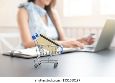 Close up shoppinig cart and credit cart with Freelancer business woman using computer laptop and credit cart to shopping online background in cafe.