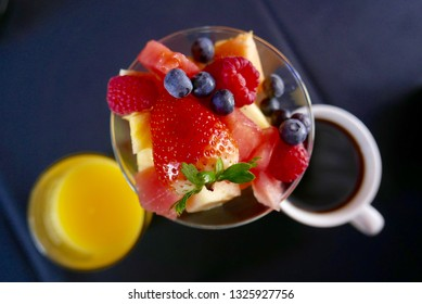 Close up shot from above of a breakfast setting with fresh fruit in a glass, orange juice, and coffee on a dark table cloth background