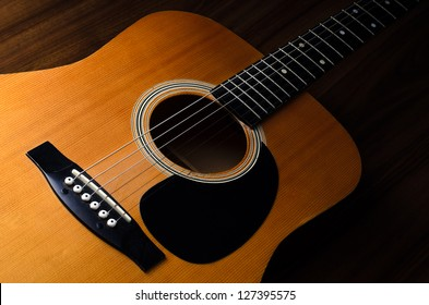 Close up shot of acoustic guitar on wooden table - low key