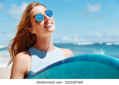 Close up shot of adorable young sunburnt female wears sunglasess, stands on sandy coastline near blue ocean or sea, enjoys summer sunny day and sunshine outdoor. Recreation and people concept