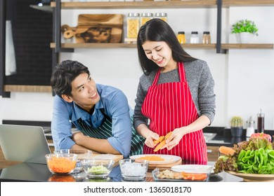 Close up shot of Asian couple in apron, man make eye contact with woman that grates the carrot into strips, in kitchen, concept for happy lover.