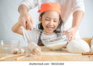 Close up shot Asian little girl holding stainless steel whisk and bakery dough flour in glass bowl and mother hands, shallow depth of field