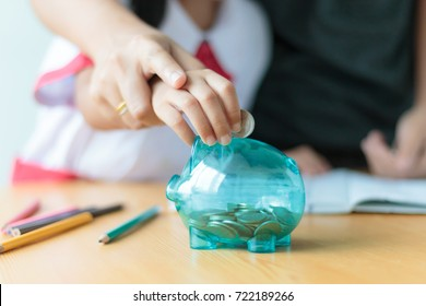 Close up shot Asian little girl in Thai student kindergarten uniform with mother hand putting money coin into clear piggy bank saving money for education concept shallow depth of field select