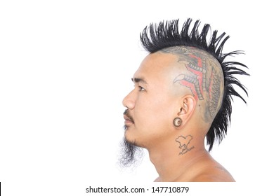 close up shot of asian punk's head with mohawk hair style, tattoo on head and ear piercing isolated on a white background